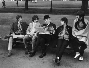 Extravagantly dressed British pop group The Beatles sits on a park bench on either side of an unidentified man in a suit and bowler hat who reads a newspaper in Hyde Park. London, England, May 19, 1967. Pictured are, from left, John Lennon (1940 - 1980), George Harrison (1943 - 2001), unidentifed man, Paul McCartney and Ringo Starr. (Photo by Marvin Lichtner/The LIFE Images Collection/Getty Images)